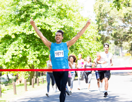 marathon: Excited male runner crossing the finshline of a marathon