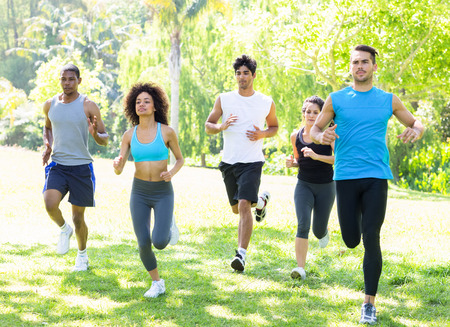 Group of people running together for fitness in the park photo