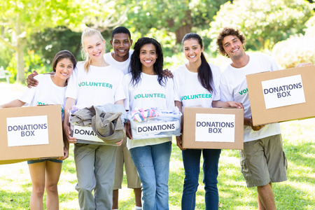 donations: Group portrait of happy volunteers carrying donation boxes in park Stock Photo