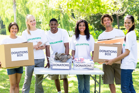 volunteerism: Portrait of young confident volunteers with donation boxes in park