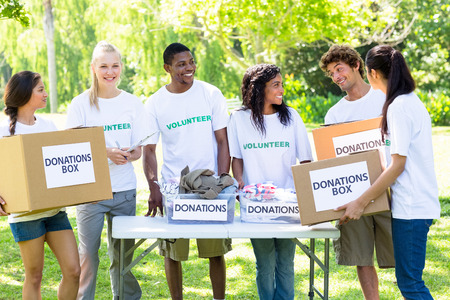 unifrom: Group of male and female volunteers with donation boxes in park