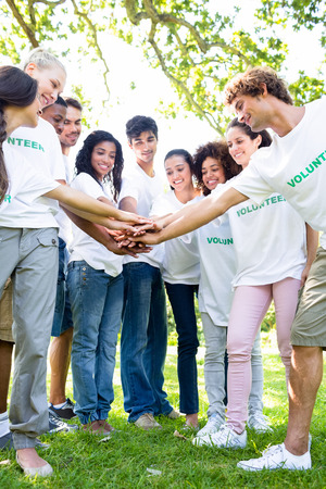 Group of multiethnic environmentalists stacking hands in park