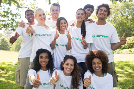 selfless: Group portrait of confident volunteers gesturing thumbs up in park