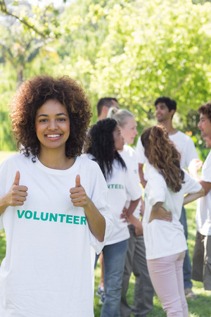 environmental conversation: Confident female volunteer gesturing thumbs up with friends disucssing in background