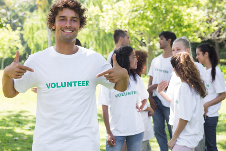 volunteerism: Portrait of male volunteer pointing at tshirt with friends in background