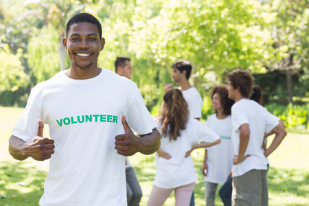 Portrait of smiling volunteer showing thumbs up with friends disucssing in background photo