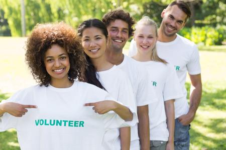 altruismo: Retrato del ambientalista muestra voluntario para camisetas con amigos de pie en la fila detr�s de