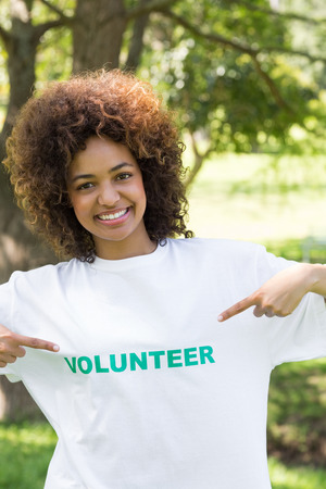 Portrait of confident environmentalist pointing at volunteer tshirt in park photo