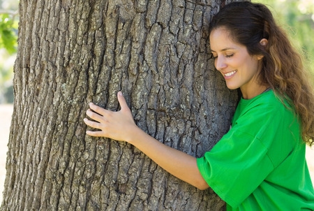 altruism: Sonreír ecologista femenino tronco del árbol abrazos en el parque