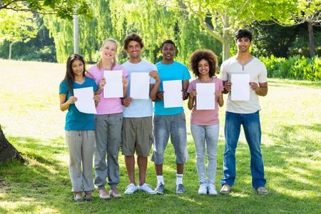 blank papers: Group portrait of multiethnic friends  holding blank papers on campus Stock Photo