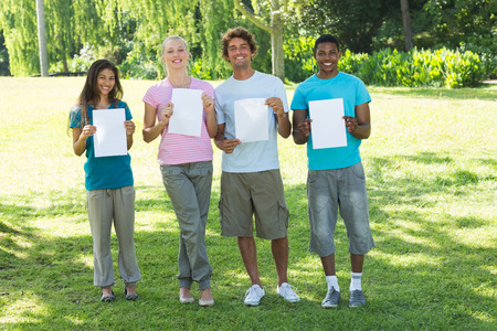 blank papers: Portrait of happy friends holding blank papers on campus