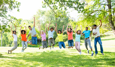 Group of excited multiethnic friends jumping in park photo