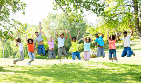 Group of cheerful multiethnic friends jumping in park photo