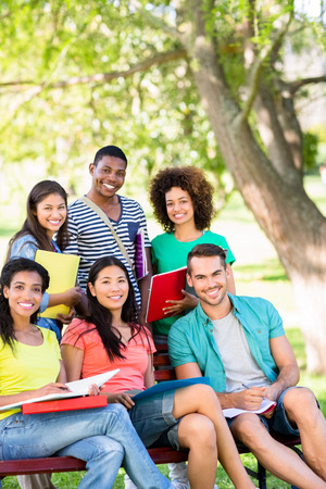 college student: Portrait of happy college students studying on bench at campus