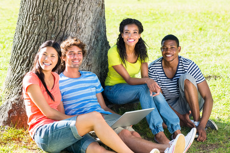 estudiantes universitarios: Estudiantes universitarios felices con el port�til sentados juntos en el campus universitario