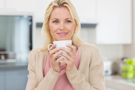 Beautiful young woman with coffee cup in the kitchen at home