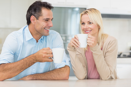 Happy couple with coffee cups in the kitchen at home photo