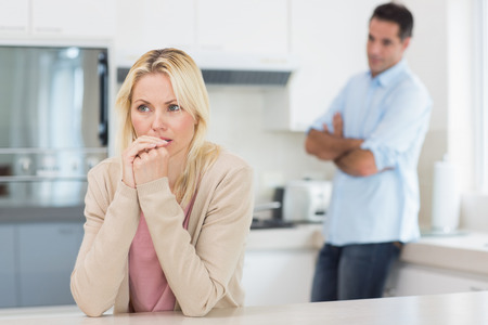 Thoughtful young woman with blurred man standing in background in the kitchen at home photo
