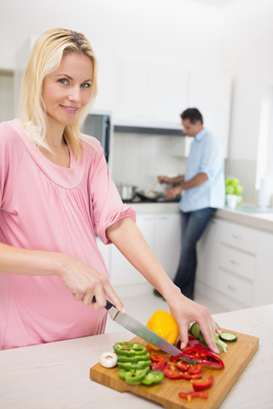 Smiling woman chopping vegetables with man doing the dishes at kitchen in the house photo