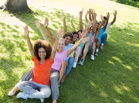 casuals: High angle view of excited friends raising hands while sitting on grass in park