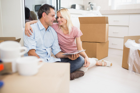 Portrait of a smiling couple using digital tablet amid boxes in a new house photo