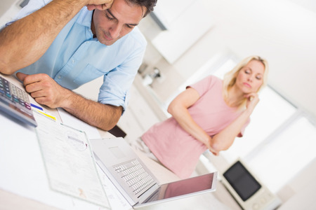 Worried couple with bills and laptop in the kitchen at home photo