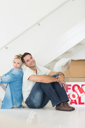 Side view portrait of a smiling couple with boxes in a new house photo