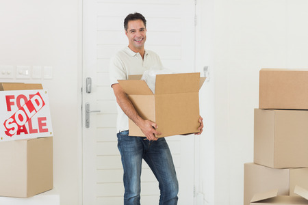 Portrait of a smiling man carrying boxes in a new house photo
