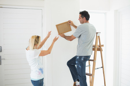 property ladder: Rear view of a couple decorating their new house