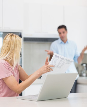 Woman and man with laptop and bill in the kitchen at home photo