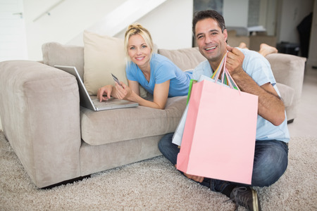 Portrait of a smiling couple doing online shopping through computer and credit card at home photo