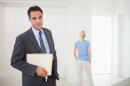 Portrait of a well dressed real estate agent with blurred woman in the background photo