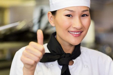 Portrait of a smiling female cook gesturing thumbs up in the kitchen photo