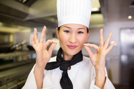 Closeup portrait of a smiling female cook gesturing okay sign in the kitchen photo