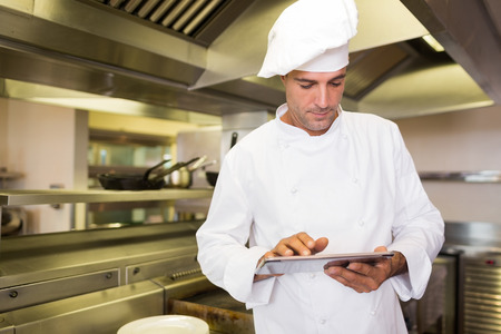 Concentrated male cook using digital tablet in the kitchen photo