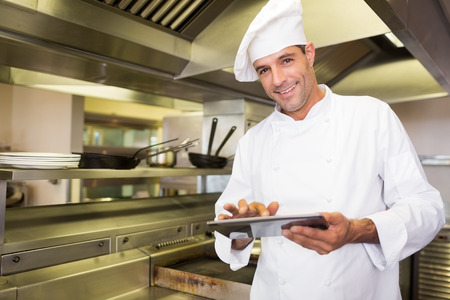 Portrait of a smiling male cook using digital tablet in the kitchen photo