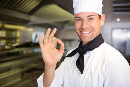 Primer retrato de un cocinero de sexo masculino sonriente que gesticula la muestra aceptable en la cocina