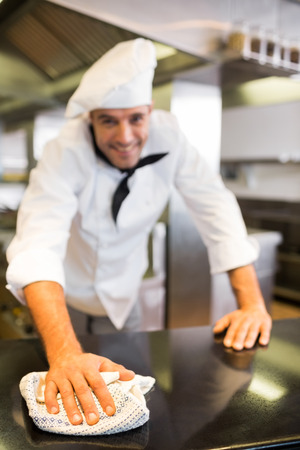 Portrait of a smiling male cook wiping the counter top in the kitchen photo
