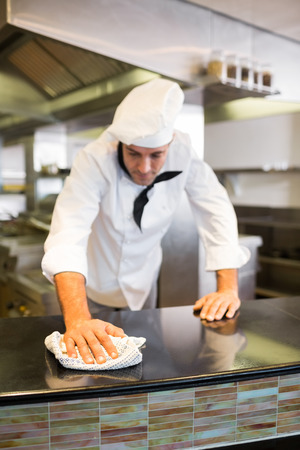 Male cook wiping the counter top in the kitchen photo