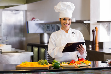 Portrait of a smiling young female chef using digital tablet while cutting vegetables in the kitchen photo