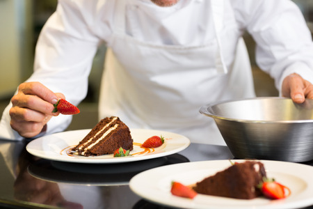 Closeup mid section of a male pastry chef decorating dessert in the kitchen photo