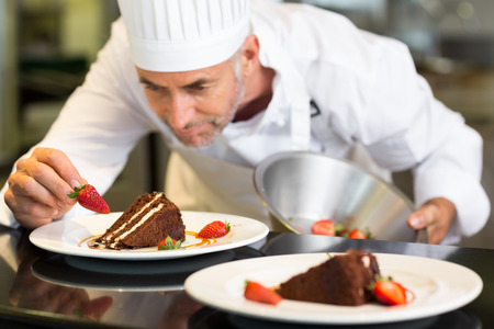 decorating: Closeup of a concentrated male pastry chef decorating dessert in the kitchen Stock Photo