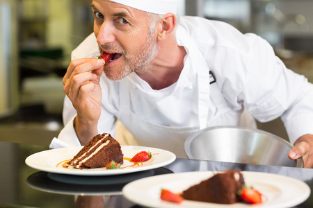 Closeup portrait of a smiling male pastry chef eating strawberry by dessert in the kitchen photo