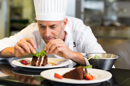 dessert stand: Closeup of a concentrated male pastry chef decorating dessert in the kitchen Stock Photo