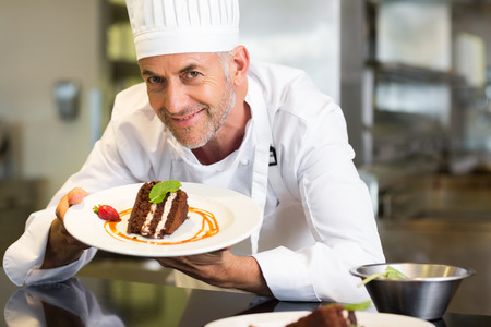 Closeup portrait of a smiling male pastry chef with dessert in the kitchen photo