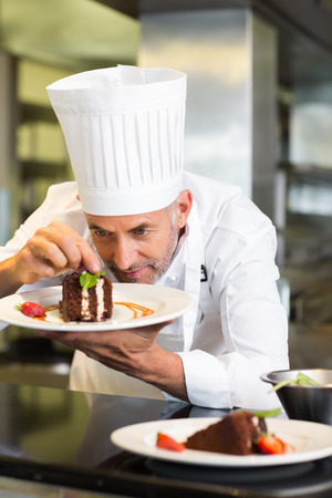 Closeup of a concentrated male pastry chef decorating dessert in the kitchen photo