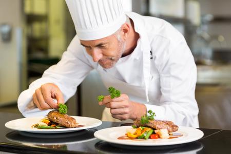 chef cocinando: Primer plano de un chef masculina concentrada adornar los alimentos en la cocina