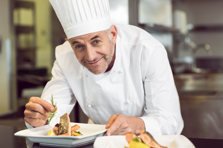 garnishing: Closeup of a smiling male chef garnishing food in the kitchen
