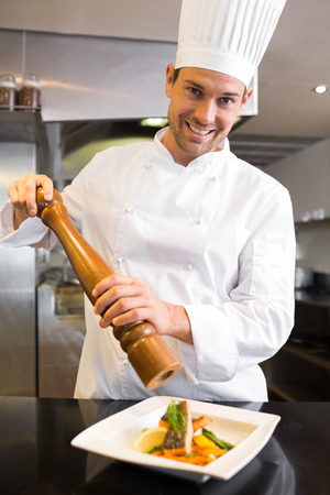 Portrait of a smiling male cook grinding pepper on food in the kitchen photo