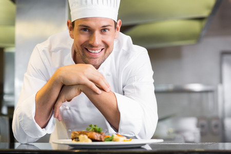 chefs: Portrait of a smiling male chef with cooked food standing in the kitchen Stock Photo